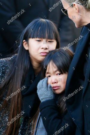 French rock star Johnny Hallyday's widow Laetitia, right, his adopted daughters Jade, left, and Joy, react as they arrive at La Madeleine church for Johnnny Hallyday's funeral ceremony in Paris, Saturday, Dec.9, 2017. France is bidding farewell to its biggest rock star, honoring Johnny Hallyday with an exceptional funeral procession down the Champs-Elysees, a presidential speech and a motorcycle parade, all under intense security