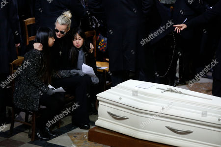 Johnny Hallyday's wife, Laetitia Hallyday, and their two children, Jade, left, and joy, right, attend the funeral service for late French rocker Johnny Hallyday at the Madeleine church, in Paris, France, . France is bidding farewell to its biggest rock star, honoring Johnny Hallyday with an exceptional funeral procession down the Champs-Elysees, a presidential speech and a motorcycle parade ? all under intense security