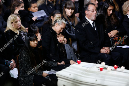 Johnny Hallyday's wife, Laetitia Hallyday, and their two children, Jade, left, and joy, right, attend the funeral service for late French rocker Johnny Hallyday at the Madeleine church, in Paris, France, . French actor Jean Reno is seated at right. France is bidding farewell to its biggest rock star, honoring Johnny Hallyday with an exceptional funeral procession down the Champs-Elysees, a presidential speech and a motorcycle parade ? all under intense security