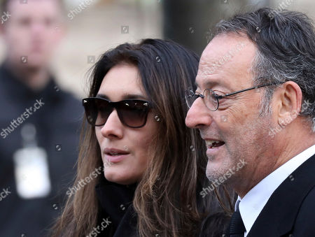 French actor Jean Reno and his wife British model Zofia Borucka leave after French rock star Johnny Hallyday's funeral ceremony in Paris, Saturday, Dec.9, 2017. France is bidding farewell to its biggest rock star, honoring Johnny Hallyday with an exceptional funeral procession down the Champs-Elysees, a presidential speech and a motorcycle parade, all under intense security