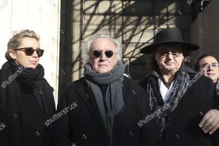 French singer Didier Barbelivien, center, wife Laure and French cook Marc Veyrat, right, arrive at La Madeleine Church prior to the funeral ceremony to late French rock singer Johnny Hallyday in Paris. France is bidding farewell to its biggest rock star, honoring Johnny Hallyday with an exceptional funeral procession down the Champs-Elysees, a presidential speech and a parade of motorcyclists ? all under intense security