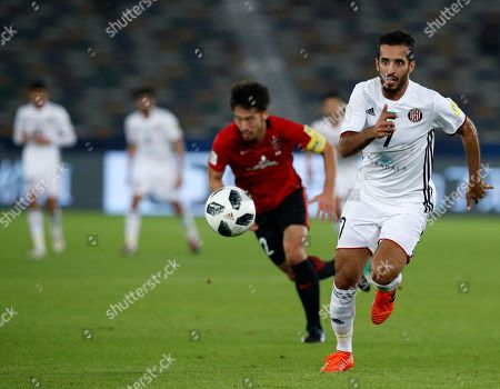 Al Jazira's Ali Mabkhout, right, and Japan's Urawa Reds Yuki Abe run for the ball during the Club World Cup soccer match between Al Jazira Club and Urawa Reds at Zayed sport city in Abu Dhabi, United Arab Emirates