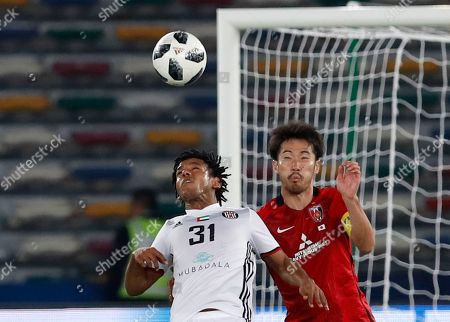 Al Jazira's Romarinho, left, challenges for the ball with Japan's Urawa Reds Yuki Abe during the Club World Cup soccer match between Al Jazira Club and Urawa Reds at Zayed sport city in Abu Dhabi, United Arab Emirates