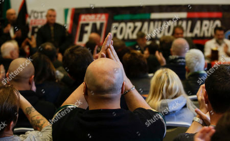 A man applauds as Italy's neo-fascist Forza Nuova leader Roberto Fiore speaks during a press conference, in Como, Italy, . Italy's governing Democrats have led a rally to warn about fascism's making a comeback in the nation, which had suffered under fascist dictator Benito Mussolini. Several thousand people turned out in Como, northern Italy, where recently right-wing extremists interrupted an NGO meeting about migrants' housing. Earlier this week, a neo-fascist party attacked the Rome office of a liberal newspaper