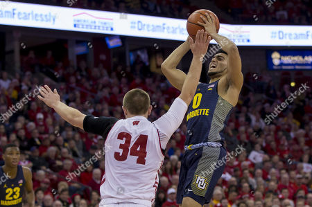 Stock Photo of Marquette Golden Eagles guard Markus Howard #0 goes up for a shot over Wisconsin Badgers guard Brad Davison #34 during the NCAA Basketball game between the Marquette Golden Eagles and the Wisconsin Badgers at the Kohl Center in Madison, WI. Marquette defeated Wisconsin 82-63