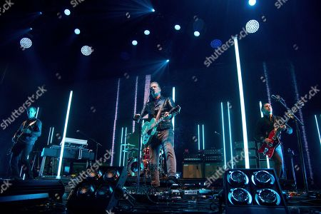 Stock Image of Dean Fertita, Josh Homme, Michael Shuman. Dean Fertita, from left, Josh Homme and Michael Shuman of Queens of the Stone Age perform at the 2017 KROQ Almost Acoustic Christmas at The Forum, in Inglewood, Calif
