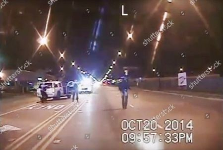 FILE - In this Oct. 20, 2014 file image taken from dash-cam video provided by the Chicago Police Department, Laquan McDonald, right, walks down the street moments before being fatally shot by Chicago Police officer Jason Van Dyke in Chicago. Three Chicago police officers have been indicted on felony charges alleging they conspired to cover up the fatal shooting of black teen Laquan McDonald by a white officer. The three officers, Thomas Gaffney, David March and Joseph Walsh, were each charged, with conspiracy, official misconduct and obstruction of justice