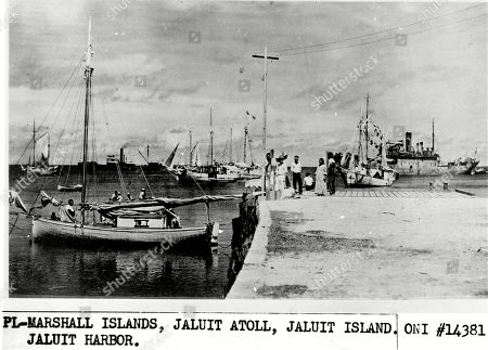 "This undated photo discovered in the U.S. National Archives by Les Kinney shows people on a dock in Jaluit Atoll, Marshall Islands. A new documentary film proposes that this image shows aviator Amelia Earhart, seated third from right, gazing at what may be her crippled aircraft loaded on a barge. The documentary ""Amelia Earhart: The Lost Evidence,"" which airs, on the History channel, argues that Earhart and her navigator, Fred Noonan, crash-landed in the Japanese-held Marshall Islands, were picked up by Japanese military and that Earhart was taken prisoner"
