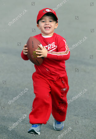 David Gallagher, 3, of Plainview, N.Y., carries a football before an NFL football game between the Buffalo Bills and the San Francisco 49ers, in Orchard Park, N.Y