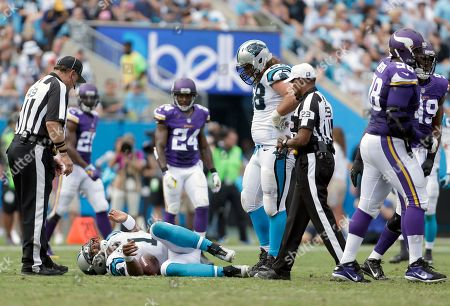Rich Hall, Jerome Boger, Cam Newton, Andrew Norwell. Umpire Rich Hall (49) and Referee Jerome Boger and Carolina Panthers' Andrew Norwell (68) look on as Panthers' quarterback Cam Newton (1) lies in pain on the turf with the Minnesota Viking defense walks to the huddle during the first half of an NFL football game in Charlotte, N.C., . The Vikings won 22-10
