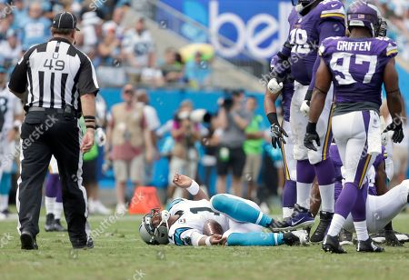 Rich Hall, Cam Newton. Umpire Rich Hall (49) looks on as Carolina Panthers' Cam Newton (1) lies in pain on the turf with the Minnesota Viking defense standing above during the first half of an NFL football game in Charlotte, N.C., . The Vikings won 22-10