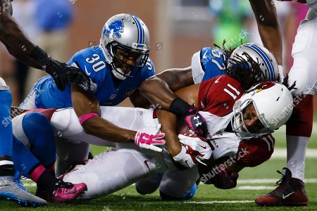 Larry Fitzgerald, Josh Wilson, Josh Bynes. Arizona Cardinals wide receiver Larry Fitzgerald (11) is tackled by Detroit Lions defensive back Josh Wilson (30) and outside linebacker Josh Bynes (57) during an NFL football game at Ford Field in Detroit