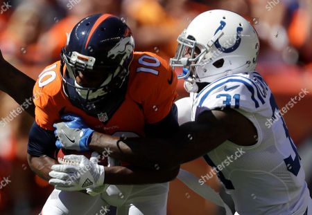 Denver Broncos wide receiver Emmanuel Sanders, left, is tackled by Indianapolis Colts cornerback Antonio Cromartie during the first half in a NFL football game, in Denver