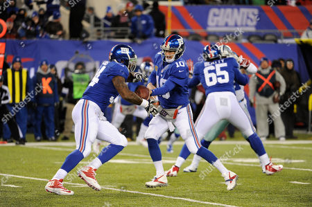 Stock Photo of Eli Manning, Brandon Jacobs. New York Giants quarterback Eli Manning (10) hands the ball off to running back Brandon Jacobs during the first half of an NFL football game against the Dallas Cowboys, in East Rutherford, N.J