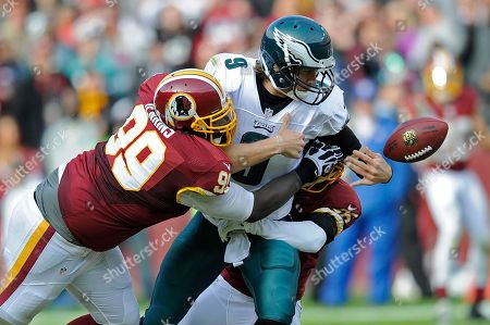 Nick Foles, Jarvis Jenkins. Philadelphia Eagles quarterback Nick Foles looses the ball on a hit from Washington Redskins defensive end Jarvis Jenkins nd cornerback Josh Wilson during the first half of an NFL football game n Landover, Md