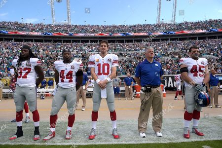 Stock Photo of Terrell Manning, Andre Williams, Eli Manning, Pat Flaherty, Henry Hynoski. New York Giants linebacker Terrell Manning (97), running back Andre Williams (44), quarterback Eli Manning (10), offensive line coach Pat Flaherty, second from right, and fullback Henry Hynoski (45) stand on the sideline for the singing of the national anthem prior to an NFL football game against the Jacksonville Jaguars in Jacksonville, Fla