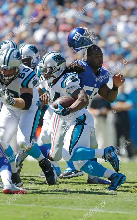 Keith Rivers, DeAngelo Williams. New York Giants' Keith Rivers (55) loses his helmet as Carolina Panthers' DeAngelo Williams (34) slips by during the first half of an NFL football game in Charlotte, N.C., . The Panthers won 38-0
