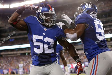 New York Giants middle linebacker Jon Beason (52) celebrate with teammate Devon Kennard (59) after breaking up a pass to Jacksonville Jaguars' Denard Robinson during the first half of a preseason NFL football game, in East Rutherford, N.J