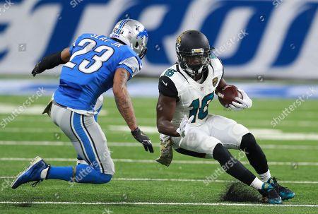 Denard Robinson, James Sample. Jacksonville Jaguars running back Denard Robinson (16) tries to avoid Jacksonville Jaguars safety James Sample (23) during an NFL football game in Detroit