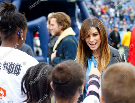 Lead singer Rachel Reinert from the award-winning and critically-acclaimed trio Gloriana talks with children before she went out to sing the National Anthem before an NFL football game, in Nashville, Tenn