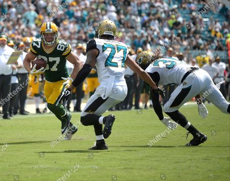 Green Bay Packers wide receiver Jordy Nelson (87) looks to get past Jacksonville Jaguars cornerback Dwayne Gratz (27) and cornerback Davon House, right, after a reception during the second half of an NFL football game in Jacksonville, Fla