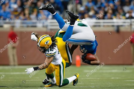 Stock Photo of Morgan Burnett, Brandon Pettigrew. Green Bay Packers free safety Morgan Burnett (42) upends Detroit Lions tight end Brandon Pettigrew (87) in the second half of an NFL football game at Ford Field in Detroit
