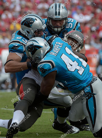 Stock Photo of Carolina Panthers defenders Chase Blackburn (93), Luke Kuechly (59) and Roman Harper (41) stop Tampa Bay Buccaneers running back Doug Martin during the second quarter of an NFL football game, in Tampa, Fla
