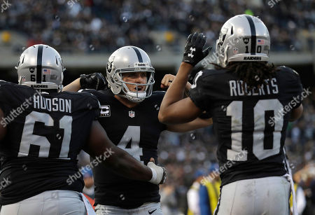 Derek Carr, Rodney Hudson, Seth Roberts. Oakland Raiders quarterback Derek Carr (4) celebrates with guard Rodney Hudson (61) and wide receiver Seth Roberts (10) during the second half of an NFL football game against the Carolina Panthers in Oakland, Calif