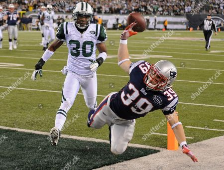 New England Patriots' Danny Woodhead dives for an incomplete pass as New York Jets defensive back Donald Strickland (30) looks on during the first quarter of an NFL football game in East Rutherford, N.J