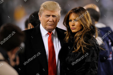 Businessman Donald Trump and his wife Melania Knauss Trump on the sidelines before an an NFL football game between the New York Jets and the New England Patriots in East Rutherford, N.J
