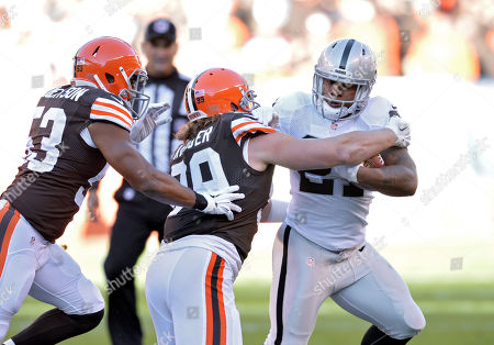 Maurice Jones-Drew, Paul Kruger. Oakland Raiders running back Maurice Jones-Drew is stopped for a loss by Cleveland Browns outside linebacker Paul Kruger (99) in the first quarter of an NFL football game, in Cleveland