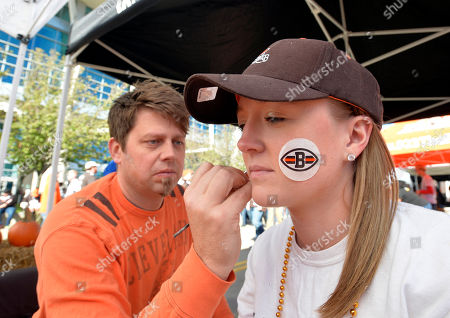 Rachael Casse gets her face painted by Jeremy Miller before an NFL football game between the Oakland Raiders and Cleveland Browns, in Cleveland