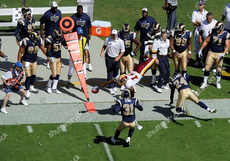 Malcolm Kelly, Justin King, Ronald Bartell. Washington Redskins wide receiver Malcolm Kelly (12) dives in front of St. Louis Rams cornerback Justin King (31) and Ronald Bartell (24) for the first down marker during the first half of an NFL football game, in Landover, Md