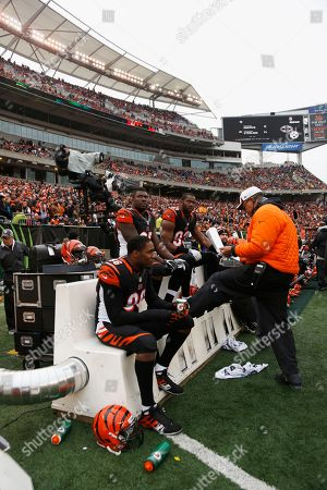Carlos Dunlap, Michael Johnson, Wallace Gilberry, Jay Hayes. Cincinnati Bengals players Carlos Dunlap (96), Michael Johnson (93), and Wallace Gilberry (95) sit with defensive line coach Jay Hayes on a heated bench in the first half of an NFL football game against the Baltimore Ravens, in Cincinnati