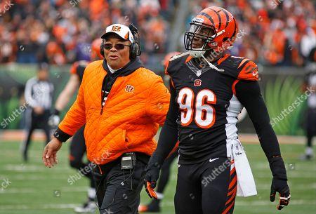 Jay Hayes, Carlos Dunlap. Cincinnati Bengals defensive lines coach Jay Hayes walks off the field with defensive end Carlos Dunlap (96) in the second half of an NFL football game against the Baltimore Ravens, in Cincinnati