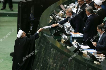 Hassan Rouhani, Ali Larijani. Iranian President Hassan Rouhani, left, submits the draft of his next year's budget bill to the parliament speaker Ali Larijani in an open session of parliament in Tehran, Iran