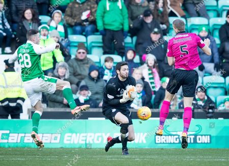 Celtic goalkeeper Craig Gordon fumbles the ball in the last minutes of the match, with Anthony Stokes of Hibernian (left) & Jozo Simunovic of Celtic (right).