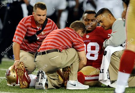 San Francisco 49ers defensive end Lawrence Okoye (98) is tended to after a play in the second half of an NFL preseason football game against the Baltimore Ravens, in Baltimore