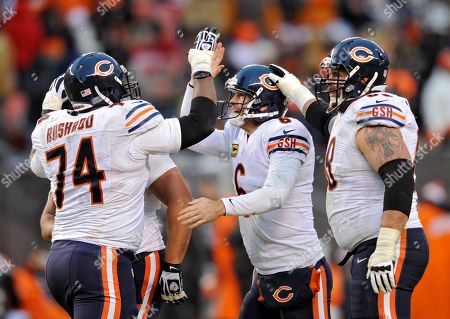 Chicago Bears quarterback Jay Cutler, center, is congratulated by his linemen after running back Michael Bush ran 40 yards for a touchdown against the Cleveland Browns in the fourth quarter of an NFL football game, in Cleveland
