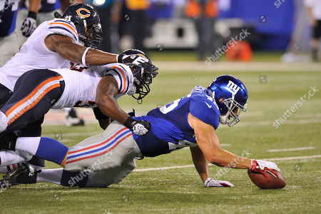 New York Giants' Henry Hynoski is tackled by Chicago Bears players during the first half of an NFL preseason football game, in East Rutherford, N.J