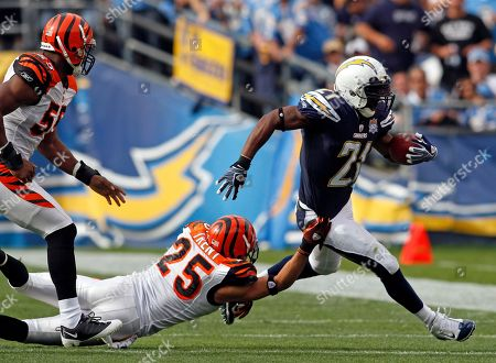 LaDainian Tomlinson, Morgan Trent, Keith Rivers. San Diego Chargers' LaDainian Tomlinson, right, escapes the tackle of Cincinnati Bengals' Morgan Trent, center and Keith Rivers, left, during an NFL football game, in San Diego