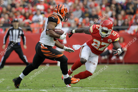 Cincinnati Bengals running back Cedric Peerman, left, tries to evade Kansas City Chiefs free safety Abram Elam (27) during the second half of an NFL football game, in Kansas City, Mo