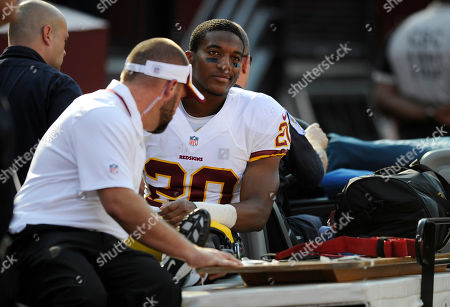 Washington Redskins cornerback Richard Crawford rides a cart off the field in the first half of an NFL preseason football game against the Buffalo Bills, in Landover, Md