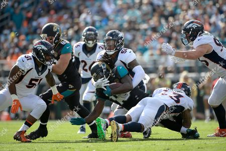 Stock Picture of Jacksonville Jaguars running back Denard Robinson (16) is tackled by Denver Broncos inside linebacker Brandon Marshall (54) and strong safety T.J. Ward (43) after rushing for yardage during the first half of an NFL football game in Jacksonville, Fla