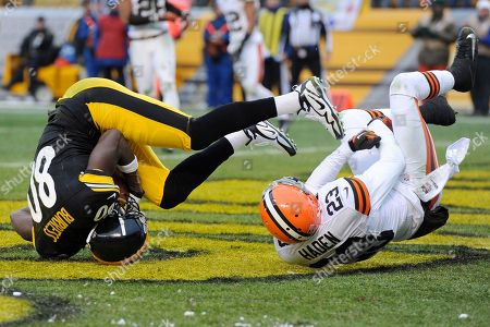 Plaxico Burress, Joe Haden. Pittsburgh Steelers wide receiver Plaxico Burress (80) tumbles in the end zone with Cleveland Browns cornerback Joe Haden (23) after making a touchdown catch in the fourth quarter of an NFL football game, in Pittsburgh