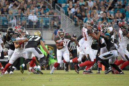 Charles Sims, Dwayne Gratz. Tampa Bay Buccaneers running back Charles Sims (34) rushes for yardage in front of Jacksonville Jaguars cornerback Dwayne Gratz (27) during the first half of an NFL preseason football game in Jacksonville, Fla