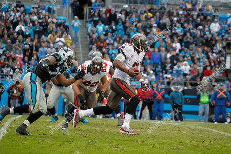 Josh Freeman, Greg Hardy, Ted Larsen. Tampa Bay Buccaneers' Josh Freeman (5) looks to get upfield as he is chased by Carolina Panthers' Greg Hardy (76) who looks to get away from the block of Tampa Bay Buccaneers' Ted Larsen (62) during the second half of an NFL football game on in Charlotte, N.C. The Buccaneers won 27-21 in overtime