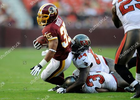 Evan Royster, Wallace Gilberry. Washington Redskins running back Evan Royster (35) carries the ball against Tampa Bay Buccaneers defensive end Wallace Gilberry (64) and Keith Tandy, (37) during an NFL preseason football game, in Landover, Md