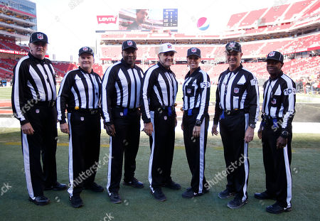 Head linesman Ed Camp, from left, field judge Jeff Lamberth, umpire Ruben Fowler, referee Peter Morelli, line judge Sarah Thomas, side judge Rob Vernatchi and back judge Dale Shaw pose for photos before an NFL football game between the San Francisco 49ers and the Arizona Cardinals in Santa Clara, Calif