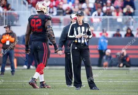 NFL line judge Sarah Thomas stands next to San Francisco 49ers defensive end Quinton Dial (92) during the first half of an NFL football game between the San Francisco 49ers and the Arizona Cardinals in Santa Clara, Calif